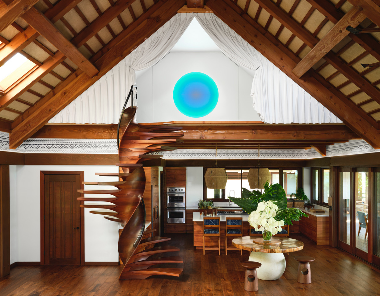 Entrance with carved wooden spiral staircase at a kite surfer's Hawaii estate. Interior by Martyn Lawrence Bullard.